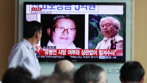 People watch a TV news broadcast showing images of Yoo Byung-eun on a screen at a Seoul railway station.