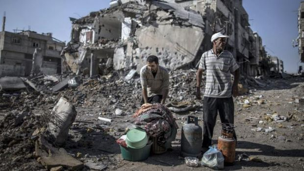 Palestinian men gather things they found in the rubble in the Shejaiya residential district of Gaza as families returned ...