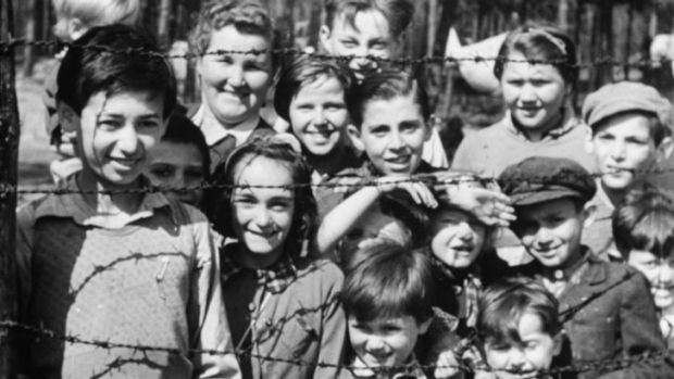 Innocence: A still of children smiling through through barbed wire, shot on April 18-20, 1945.