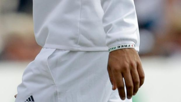 England's Moeen Ali wears a wristband as he fields during the second day of the third cricket test match of the series ...
