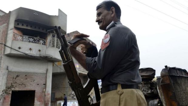 A Pakistani policeman slings his weapon as he stands guard outside the smoke-charred house of an Ahmadi Muslim resident ...