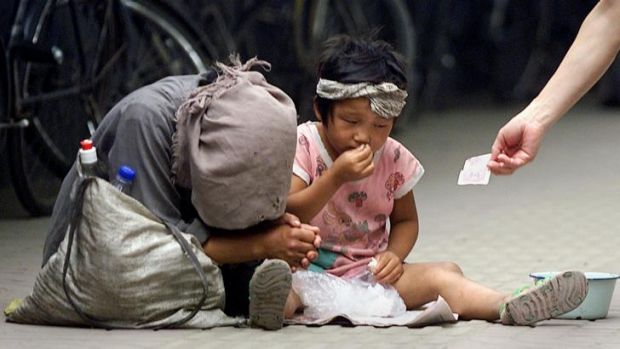Inequality poses a problem in China - and the US. A woman and a child beg on the street in Beijing.