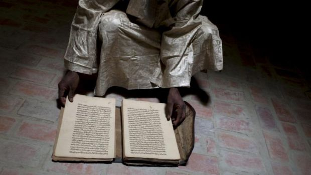 A director at the Ahmed Baba Institute, with an ancient manuscript that was saved from an attack.