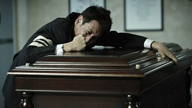 Detective Go Geon-soo (Seon-gyun Lee) weeps on his mother's coffin in <i>A Hard Day</i>.