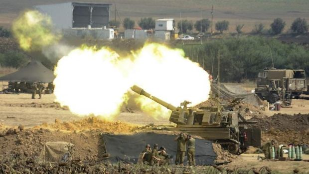 An Israeli canon fires towards the Gaza Strip from the border.