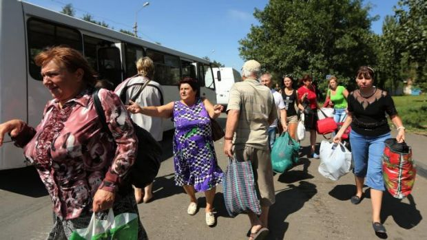 Residents of Shakhtersk run towards buses being provided by the pro-Russian rebels for people wanting to flee the town ...