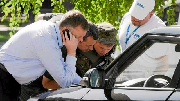 Alexander Hug, deputy head of the OSCE mission to Ukraine, left, his colleagues and a pro-Russian rebel, second right, ...