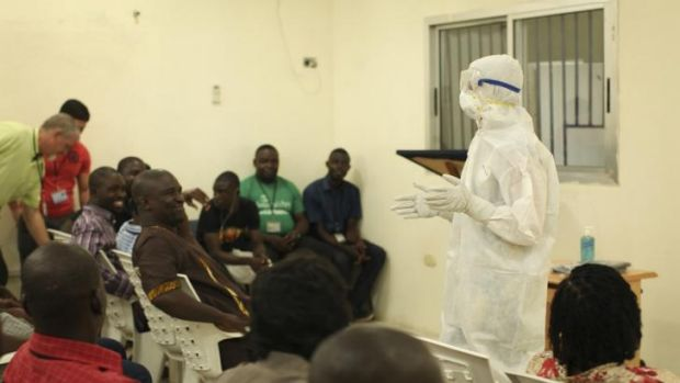 Medical personnel demonstrate protective equipment to educate team members on the Ebola virus  in Liberia.