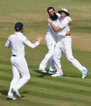 Moeen Ali is congratulated by Joe Root after taking the wicket of Cheteshwar Pujara.