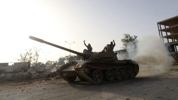 Militants raise their arms in salute next to the camp of special forces in Benghazi.
