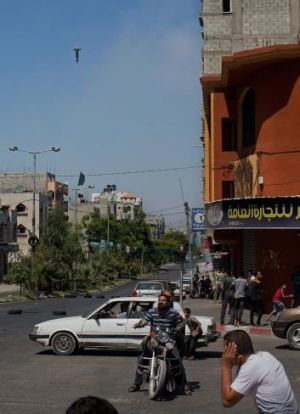 Residents in Gaza City block their ears as an Israeli ordnance finds its target.