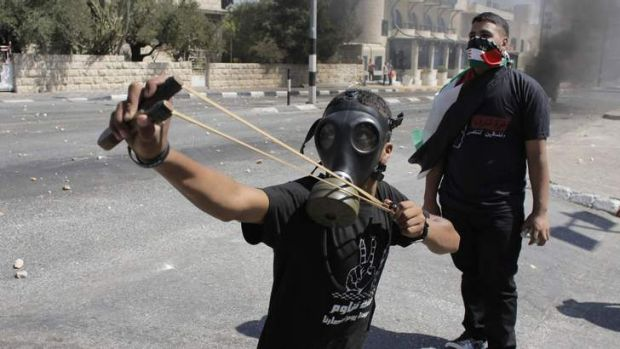 A Palestinian protester uses a slingshot during clashes with Israeli border police at a protest against the Israeli ...