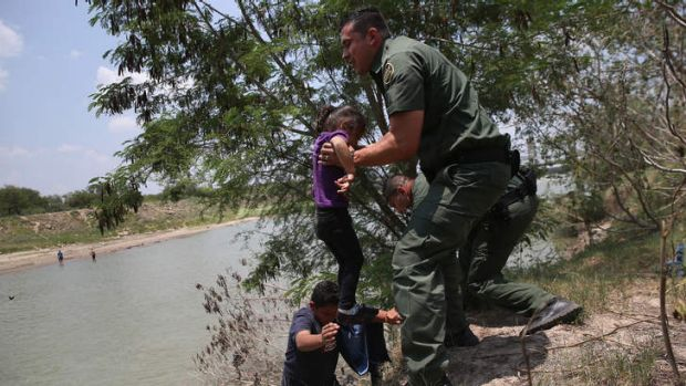 US Border Patrol agents help minors from El Salvador after they crossed the Rio Grande illegally into the United States.
