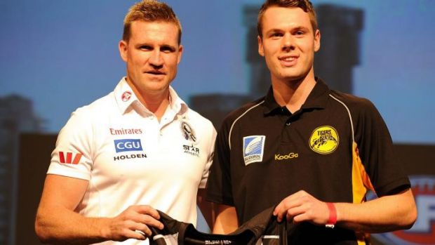 Collingwood coach Nathan Buckley presents Matthew Scharenberg with the Collingwood guernsey during the 2013 draft on ...