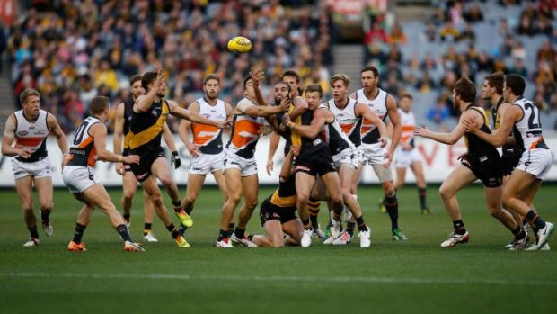 Tiger Bachar Houli handballs from the midst of a pack of players at the MCG on Saturday.