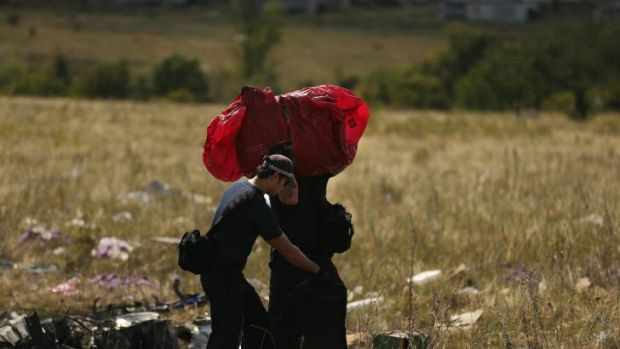A suitcase wrapped in red plastic is recovered from the MH17 crash wreckage.