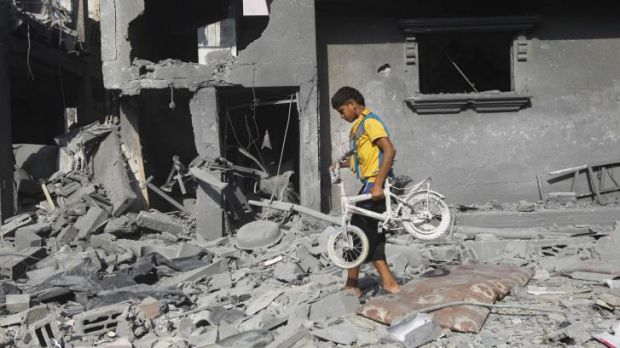A Palestinian boy carries a bicycle from the wreckage of a building in the southern Gaza Strip city of Rafah on Saturday.