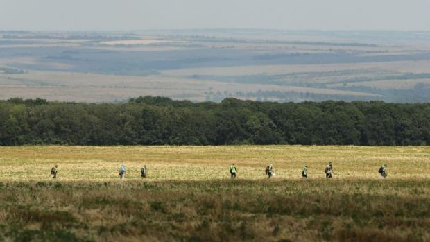 Australian Federal Police and their Dutch counterparts search a field for MH17 victims and belongings on the outskirts ...