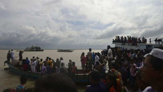 Crowds gather near the river bank where the ferry capsized.