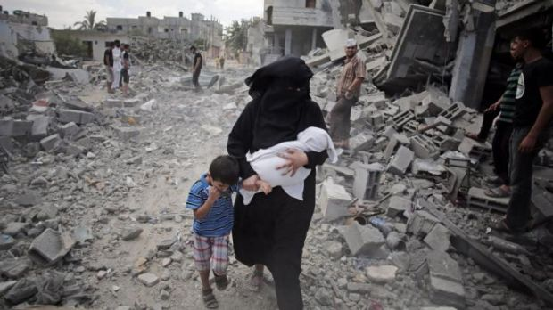 A Palestinian woman passes by rescuers inspecting the rubble following Israeli strikes on the Rafah refugee camp.