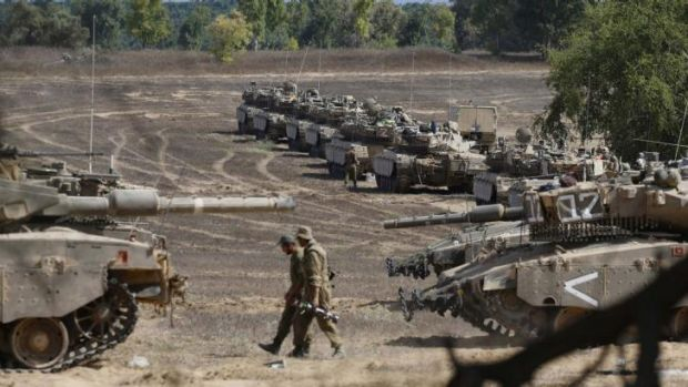 Israeli soldiers walk past tanks near the border with the Gaza Strip.
