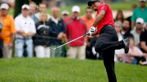Tiger Woods hits out of the rough at Firestone Country Club on Sunday..
