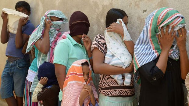 Sri Lankan asylum seekers sent back by Australia queue to enter the magistrate's court in the southern port district of ...