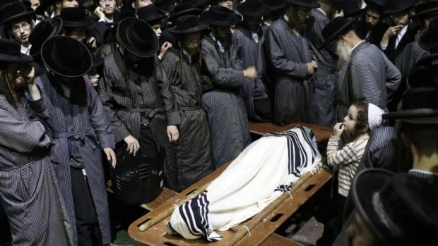 The young son of Abraham Wallace stands next to his covered body at his funeral in Jerusalem's Mea Shearim ...