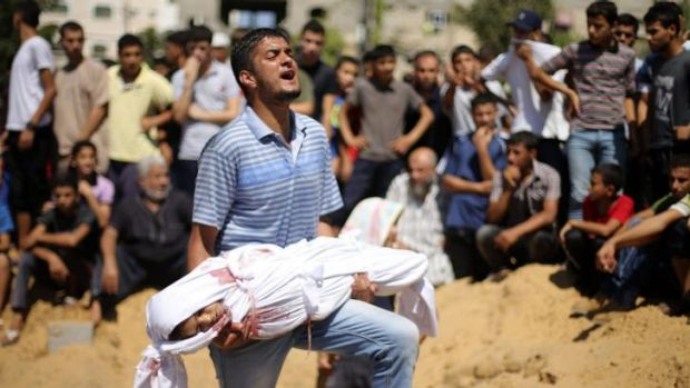 A man at a funeral in Beit Lahiya carries the body of a girl from the Abu Nejim family, whom medics said was killed ...