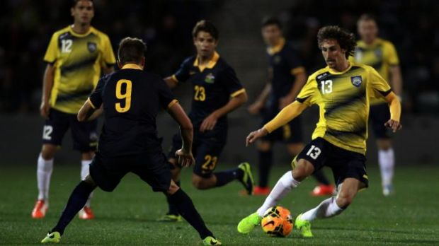 On the charge: All Stars player Albert Riera has a cut at the Young Socceroos defence.