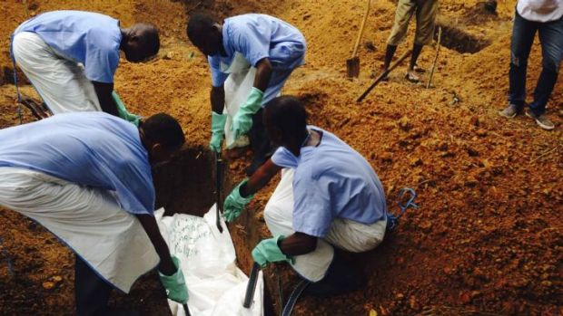 Volunteers lower a corpse, which is prepared with safe burial practices to ensure it does not pose a health risk to ...