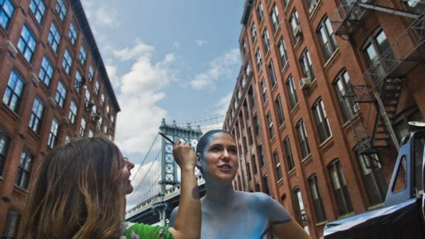 Trina Merry, left, paints model Jessica Mellow in colours of the Manhattan Bridge in the Brooklyn borough of New York.