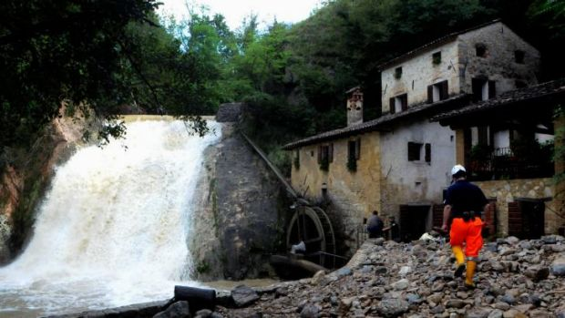 Italian rescue workers try to protect the 17th century Molinetto della Croda mill against the overflowing Lierza River ...