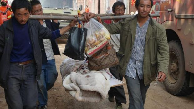 Locals carry a body out of the village of Ludian in the aftermath of the earthquake.