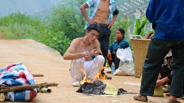 Xiao Gongchao burns paper offerings for his dead grandmother and nephew.