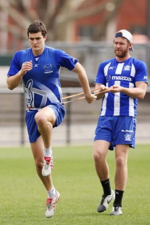 Lachlan Hansen holds back Scott Thompson during a North Melbourne training session on Wednesday.