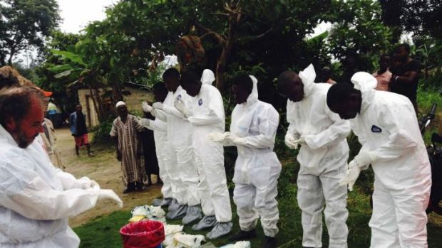Volunteers prepare to remove the bodies of people who were suspected of contracting Ebola and died in the community in ...