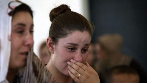 An Iraqi Yazidi woman who fled Sinjar, cries as she stands among others at a school where they are taking shelter.