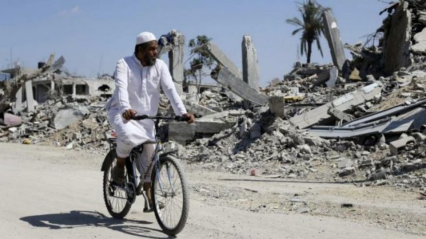 A Palestinian man cycles past the ruins of Khuza'a in the southern Gaza Strip.