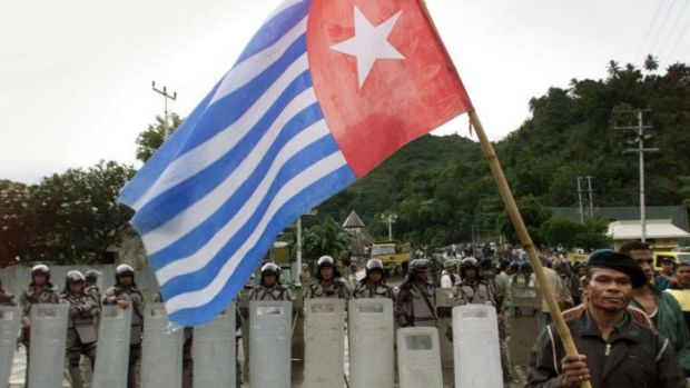 This file photo shows a West Papuan separatist carrying the banned Morning Star flag as he walks past a line of ...