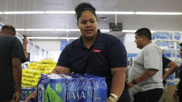 Andrea Malosa loads bottled water into her shopping cart while buying supplies in Mililani as two hurricanes  approach ...