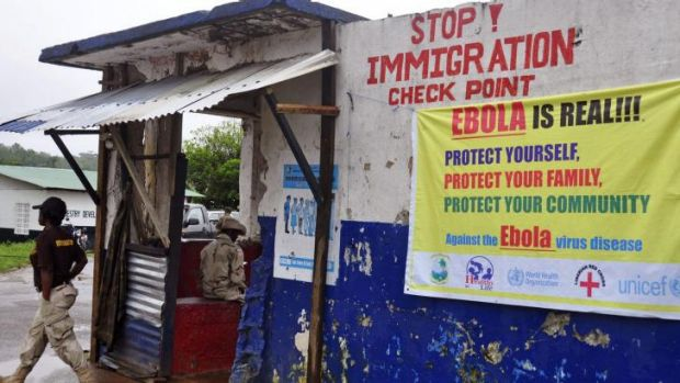 A Liberian soldier, left, mans a checkpoint to control the movement of people as authorities try to prevent the Ebola ...
