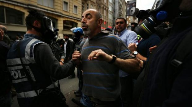 'This is where I live': Ibrahim Aktgun is grabbed by riot police during the anniversary protests in Istanbul.