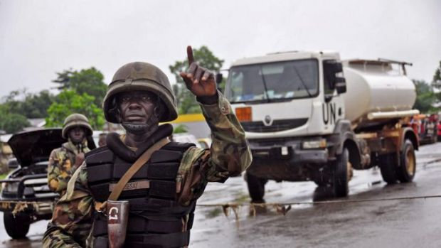 A Liberian soldiers stops people at a security checkpoint set up to clamp down on people traveling due to the Ebola ...