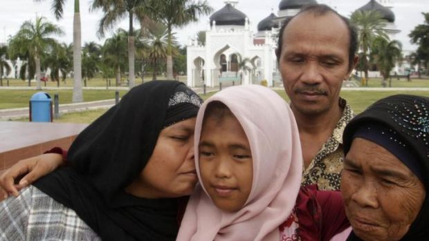 Jamaliah (left) kisses her daughter Raudhatul Jannah, 14, as the girl's father Septi Rangkuti and grandmother Sarwani ...