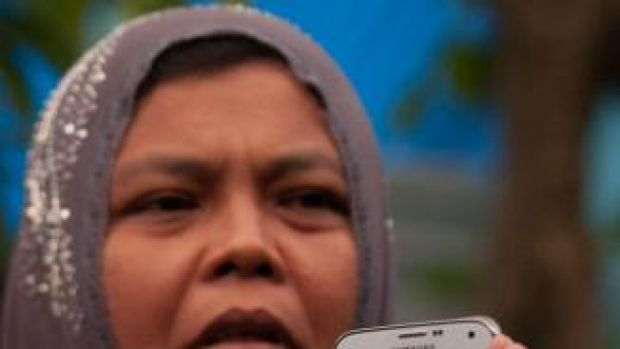 Indonesian mother Jamaliah displays a picture taken before the 2004 tsunami of her children, daughter Raudhatul Jannah ...