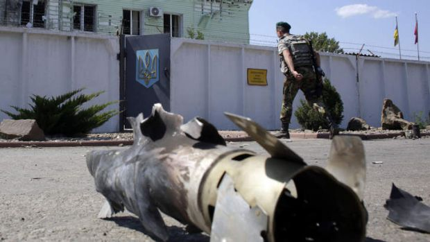An Ukrainian border guard walks to a barracks as he passes by a fragment of an exploded mine.