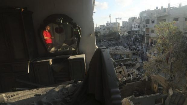 A Palestinian man inspects his house, which witnesses said was hit in an Israeli air strike, in Jabaliya refugee camp in ...