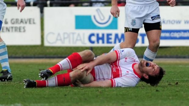 Tuggeranong's captain, Gareth Clouston in agony on the field.