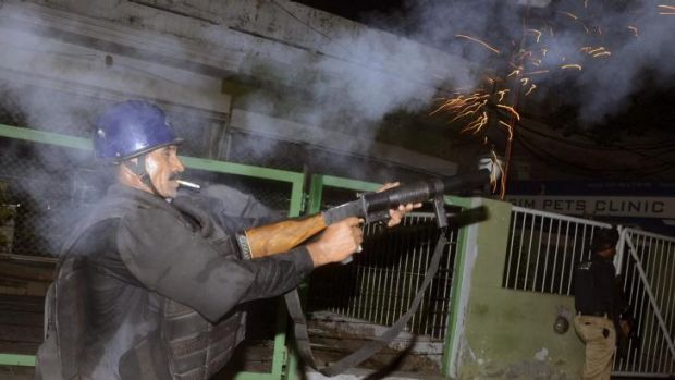 A policeman fires tear gas to disperse supporters of Muhammad Tahirul Qadri, Sufi cleric and leader of political party ...